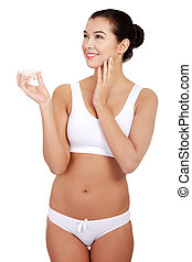 Pretty fit woman in underwear with moisturizer cream.