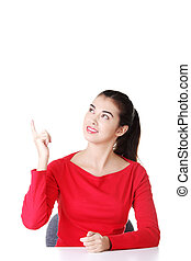 Woman sitting at the desk and pointing something - Young...