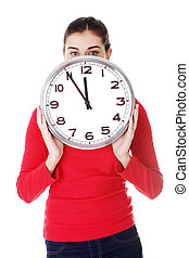 Shocked woman holding office clock, isolated on white...