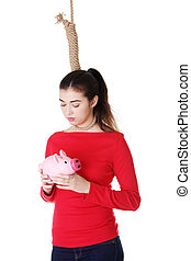 Economic crisis concept Young woman holding piggy bank going...