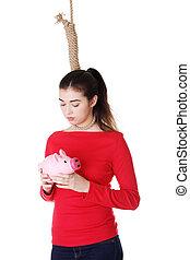 Economic crisis concept. Young woman holding piggy bank...