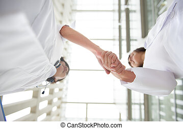 Two young medical doctors shaking hands, teamwork