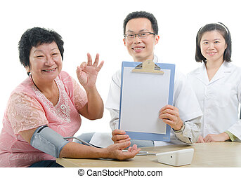 asian senior female thumbs up during medical checkup with doctor ,south east asian chinese ethnicity