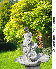 Old statue of a fountain in a shady park