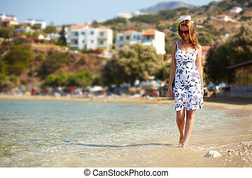 Woman on the beach - Young woman walking in water by the...