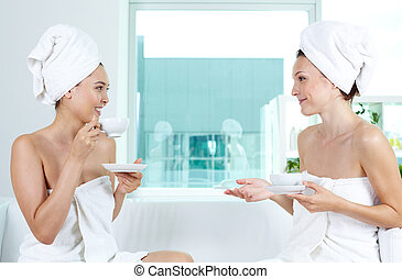 Girls talking - Girls in bath towels communicating in spa...
