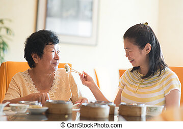 Feeding senior parent food - Asian Chinese adult daughter...