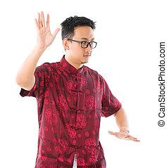 Tai chi - Southeast Asian Chinese male practicing tai chi,...