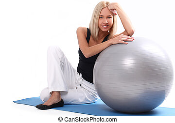 Happy and beautiful woman with fitness ball