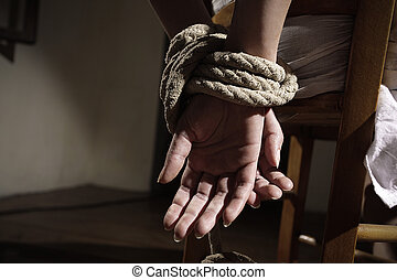 Woman prisoner - Young woman tied to a chair in a empty...