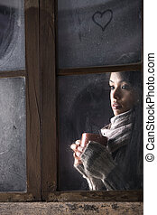 Girl behind window with a cup of coffee or tea - Portrait of...