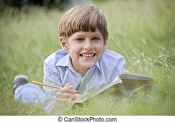Happy school boy doing homework and smiling, lying on grass...