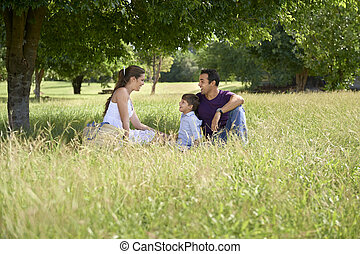 Family with happy young man, woman and child playing