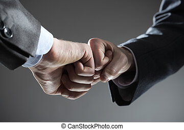 Business teamwork: two fists touching hand gesture
