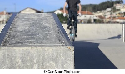 Bmx rider grinding on a concrete park on a sunny day.