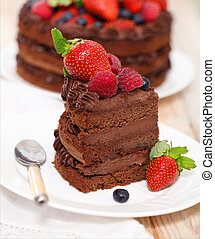 Piece of chocolate cake with icing and fresh berry on light...