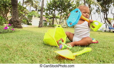 baby child playing with toys - little baby sitting on the...
