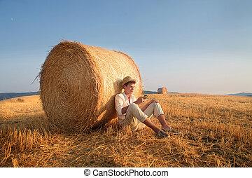 Man next haystack - Man sitting next haystack