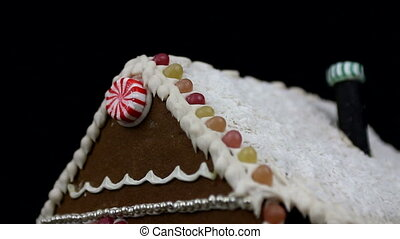 Home made gingerbread house with christmas trees on black...