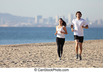Man and woman running in the beach towards the sea with a...