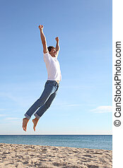 Man jumping happy in the beach with a blue sky in the...