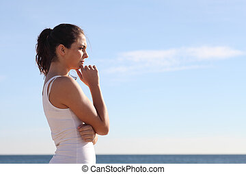 Beautiful woman thinking and watching in front the sea
