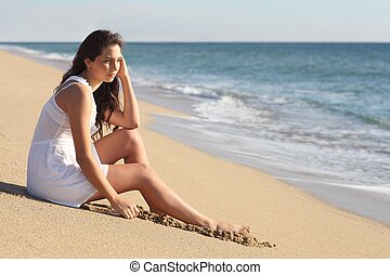 Beautiful woman thinking and watching the sea on the beach