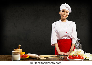 Asian woman chef standing near a kitchen table, ready for...