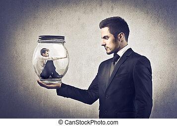 Businessman holding mini man in jar