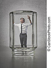 glass house - businessman in a closed jar on gray background