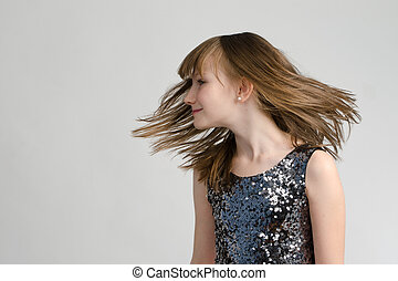 Adorable girl shaking her head with long hair, studio shot