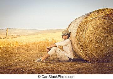 Boy next to haystack in field