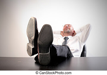 Businessman resting with feet on his desk