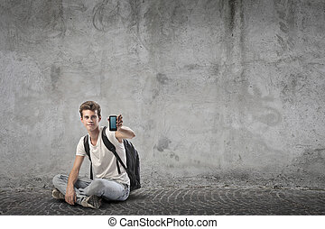 boy with telephone - young man sitting on the floor with...