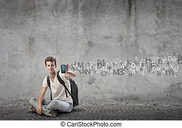 boy with phone - young man sitting on the floor with phone...