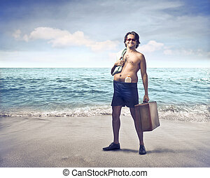 Man on beach with luggage