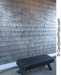 textured wood siding with bench - bench in front of a...