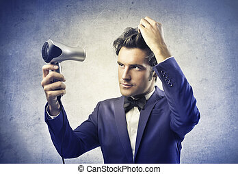 handsome man dries his hair with phone