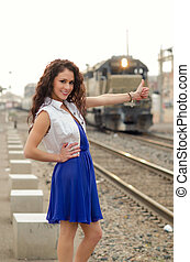 woman thumbing a ride on train - Attractive young smiling...