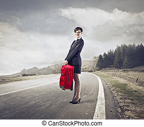 Traveller woman - Woman standing on freeway with suitcase