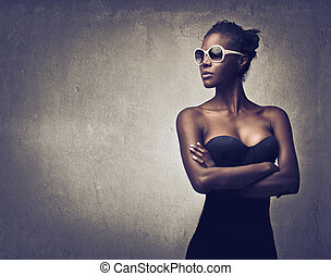 beautiful black woman with sunglasses on gray background