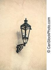 Old street light closeup on stone wall in Prague