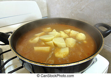 Saucepan - Potatoes cooking in hot saucepan with meat and...