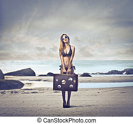 holiday - blonde woman with big suitcase on the beach