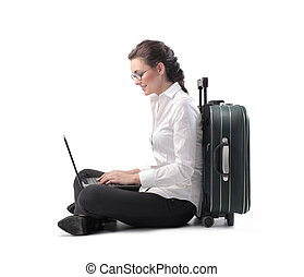 Business trip - Woman working on laptop next to suitcase
