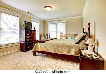 Large bright bedroom with wood furniture and beige tones