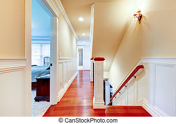 Large bright hallway with cherry hardwood and staircase.