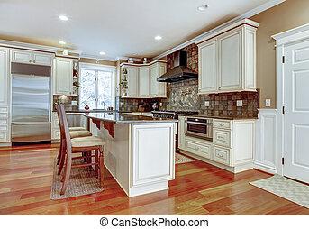 Large white luxury kitchen with cherry hardwood.