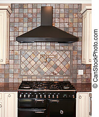 Large black kitchen stove with stone tiles and white cabinets.