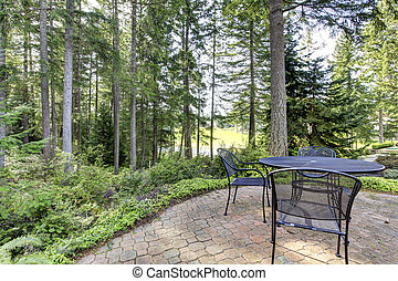 Backyard with pine trees and metal table with chairs.